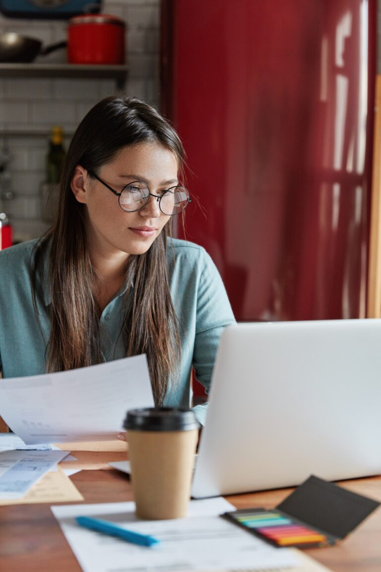 Busy financier checks accountings from papers, focused into screen of laptop computer, wears round o