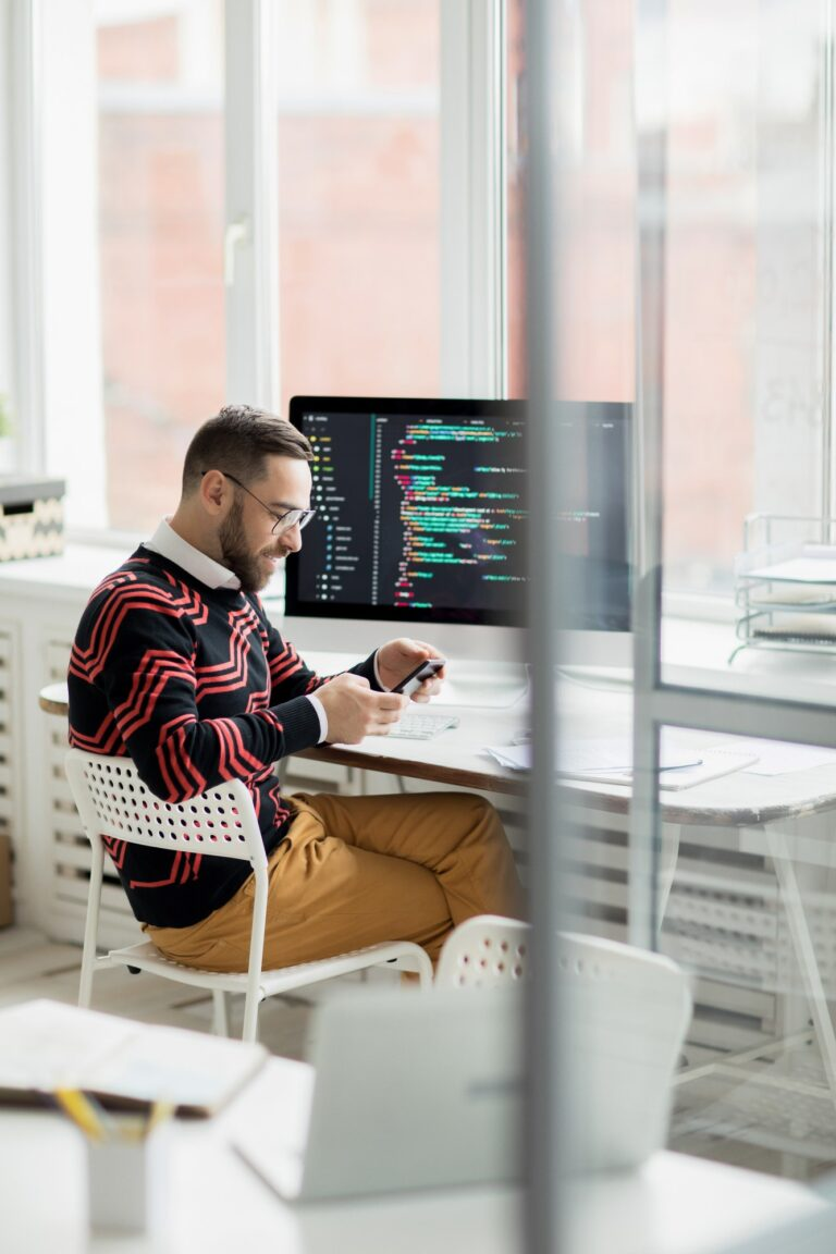 Smiling programmer working in office