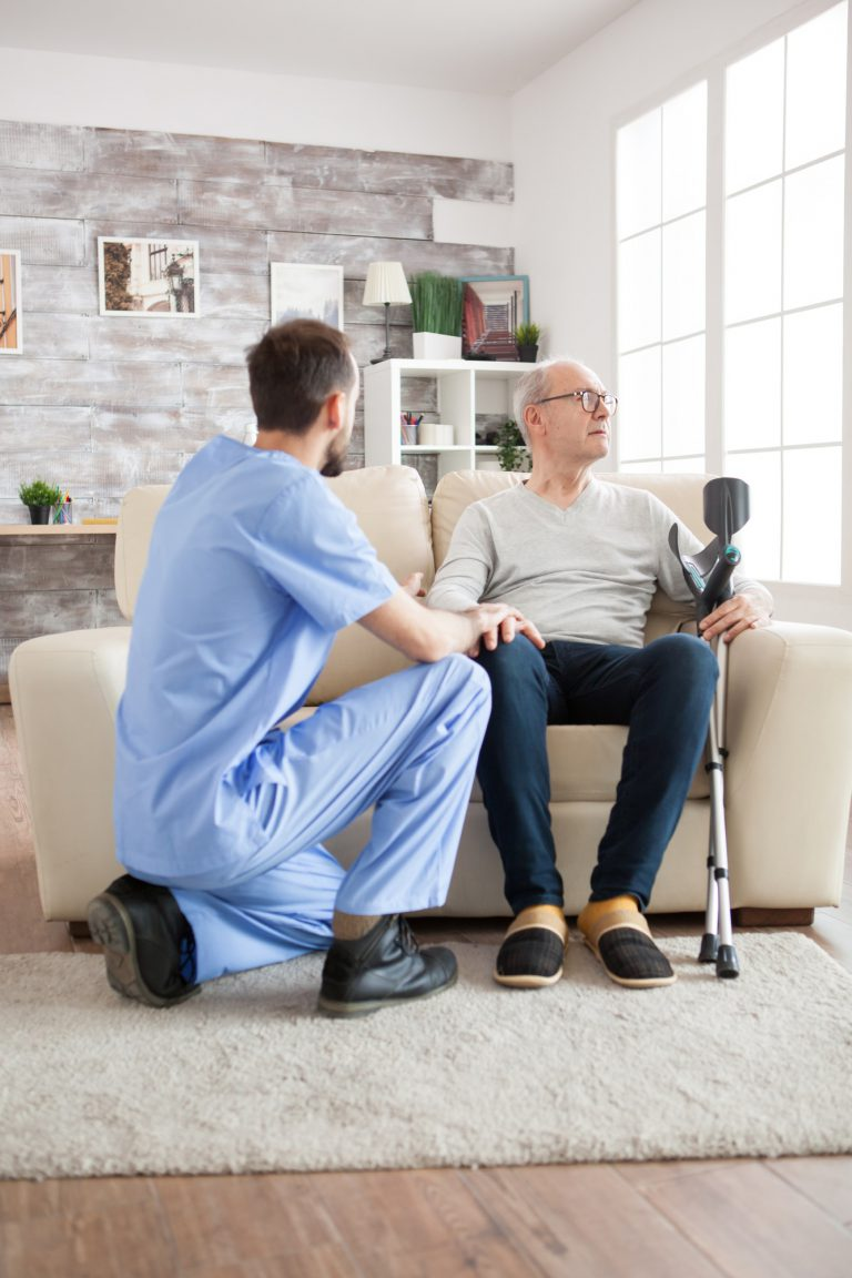 Young doctor in nursing home talking with old man
